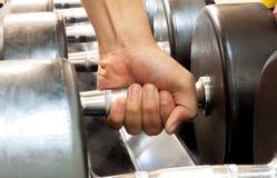 Mano alguien que lleva a cabo pesa de gimnasia en gimnasio Fotografía de archivo