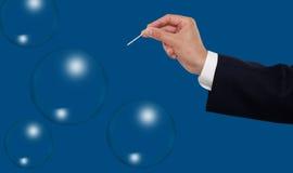 Mano alrededor para estallar una burbuja con una aguja Fotografía de archivo libre de regalías