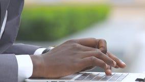 Mano americana de Cropped del hombre de negocios del hombre que sostiene el teléfono móvil mientras que mecanografía en el ordena almacen de video