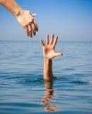 Mano amica che dà ad annegare uomo Fotografie Stock Libere da Diritti