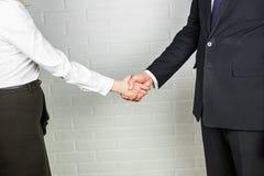 Mano amiga Hombre de negocios y empresaria que sacuden las manos en oficina Imagen de archivo