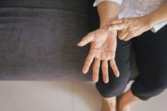 Mano anziana della donna che controlla il suo impulso con due dita sul polso immagine stock