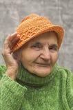 Mano anziana della tenuta della donna vicino ad un orecchio Fotografia Stock Libera da Diritti