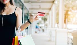Mano ascendente cercana de las mujeres que celebran la tarjeta de crédito y bolsos de compras en el centro comercial foto de archivo libre de regalías
