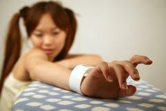 Mano asiática de la muchacha en la tabla Imagen de archivo