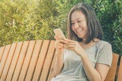 Mano asiática de la mujer joven que sostiene el teléfono móvil Fotografía de archivo libre de regalías