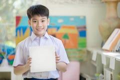 Mano asiática feliz del muchacho que lleva a cabo al tablero de papel en blanco y que mira el Ca Fotografía de archivo