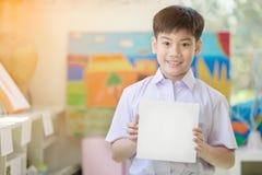 Mano asiática feliz del muchacho que lleva a cabo al tablero de papel en blanco y que mira el Ca Imagenes de archivo