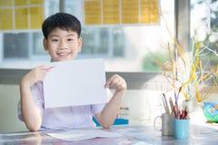 Mano asiática feliz del muchacho que sostiene la hoja en blanco del papel A4 y que la mira Fotografía de archivo libre de regalías