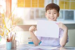 Mano asiática feliz del muchacho que sostiene la hoja en blanco del papel A4 y que la mira Imagen de archivo