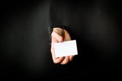 Mano attraverso carta nera Fotografia Stock Libera da Diritti