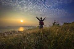 Mano in aumento di vittoria dell'uomo del Trekker al sentiero didattico con il cielo stabilito del sole Fotografie Stock Libere da Diritti