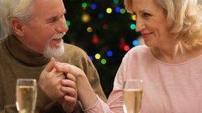 Mano baciante del signore anziano della moglie cara, cena romantica di notte di Natale stock footage