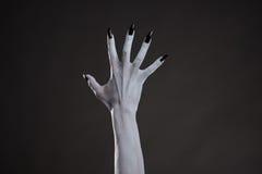 Mano bianca spettrale con i chiodi neri Immagine Stock