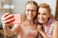 Mano bien arreglada de una muchacha que sostiene un teléfono Imágenes de archivo libres de regalías