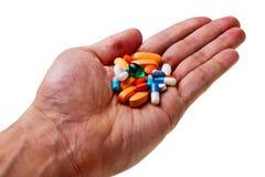 Mano blanca masculina con las píldoras coloridas. Fotos de archivo