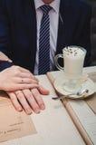 Mano cariñosa del hombre del control de la mujer Apenas pareja casada que aparece los anillos de bodas Cerca de la taza de café d Imagenes de archivo