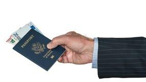 Mano caucásica mayor que sostiene el pasaporte de los E.E.U.U. con euros fotografía de archivo libre de regalías