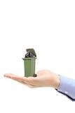 Mano caucásica que sostiene un bote de basura verde Imagen de archivo libre de regalías