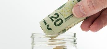 Mano caucasica che tiene venti banconote in dollari sopra il barattolo Fotografie Stock