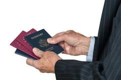 Mano caucasica senior che sceglie che passaporto per usare fotografia stock libera da diritti