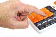Mano caucásica que hace cálculos en una naranja Imágenes de archivo libres de regalías