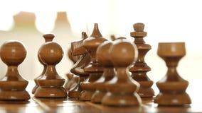 Mano cercana del hombre de la visión que juega y que se mueve estratégica un pedazo en la tabla del ajedrez almacen de video