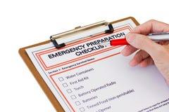 Mano che completa la lista della preparazione di emergenza Fotografia Stock