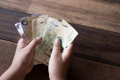Mano che conta le banconote saudite del riyal fotografie stock