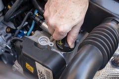 Mano che controlla il cappuccio dell'olio di un motore di automobile Fotografia Stock