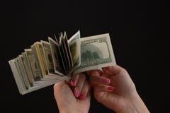 Mano che dà soldi, i dollari statunitense o USD Mani che tengono le banconote Mani che tengono una fattura del dollaro 100 fotografie stock libere da diritti