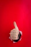 Mano che dà i pollici in su su colore rosso Immagini Stock Libere da Diritti