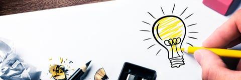 Mano che disegna lampadina su carta fotografia stock