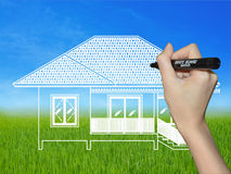 Mano che disegna una casa su un paesaggio Fotografie Stock