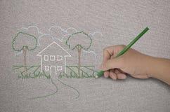 Mano che dissipa una casa con la matita verde Fotografie Stock Libere da Diritti