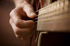 Mano che gioca chitarra acustica Fotografie Stock Libere da Diritti