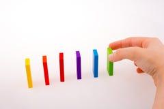 Mano che gioca con il domino colorato Fotografia Stock