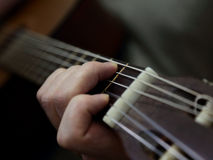 Mano che gioca corda sulla chitarra acustica Fotografie Stock Libere da Diritti