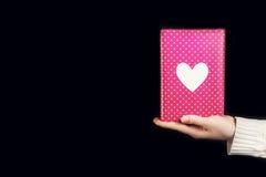 Mano che giudica regalo rosa isolato sul nero Immagine Stock