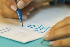 Mano che impara iscrizione nella classe con la penna blu ed il Libro Bianco fotografia stock libera da diritti