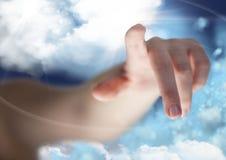 Mano che indica contro il cielo nuvoloso nel fondo Fotografie Stock
