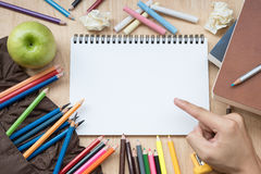 Mano che indica i rifornimenti di scuola del Libro Bianco Fotografie Stock Libere da Diritti
