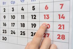 Mano che indica il giorno libero sabato su un calendario murale fotografia stock