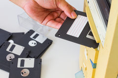 Mano che inserisce i 3 floppy disk a 5 pollici in una scanalatura di unità floppy o Immagini Stock