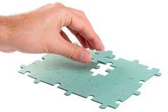 Mano che inserisce puzzle di puzzle verde Fotografia Stock Libera da Diritti