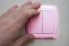 mano che lancia interruttore della luce con la parete rosa fotografia stock