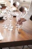 Mano che mette i vetri del champagne Fotografie Stock Libere da Diritti