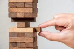 Mano che mette la torre della pila del blocco di legno, gestione dei rischi di concetto Immagine Stock Libera da Diritti