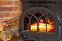 Mano che mette legno sul camino del fuoco heating fotografia stock