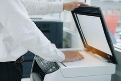 Mano che mette una carta del documento nell'analizzatore di stampante o nella macchina della copia laser in ufficio immagini stock